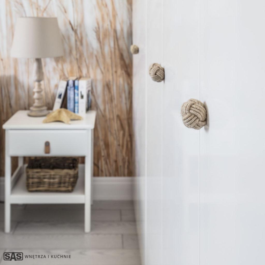 Meble w wykonaniu firmy SAS Wnętrza i Kuchnie. Projekt architekt wnętrz Emilia Strzempek Plasun. Detal: uchwyty frontów meblowych w kształcie węzłów.